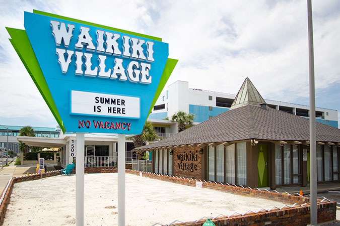 exterior signage and bocce ball court at Waikiki Village